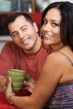 Attractive Mexican couple sitting together in a cafe photo