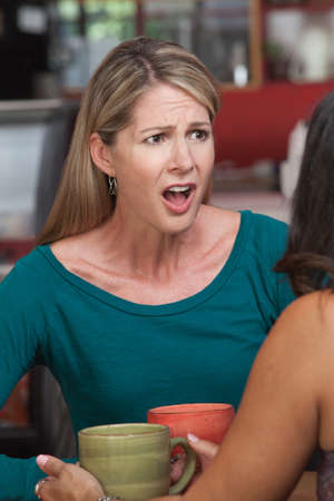 Insulted Caucasian woman across from friend in restaurant Stock Photo - 17160663