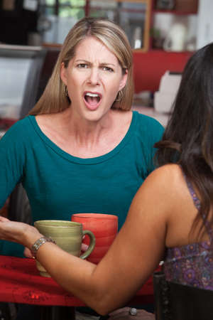 Outraged European woman across from person in a coffeehouse photo