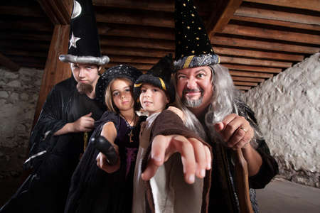 Father and children in mythical wizard costumes photo