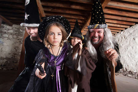 Magician father and children casting spells in a basement photo