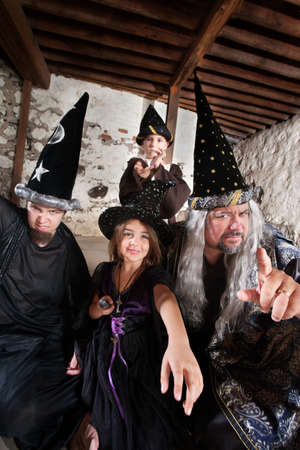 Sister and brother wizards casting spells with their father photo