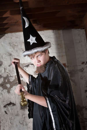 Menacing teenager dressed as wizard with tall hat and scepter photo