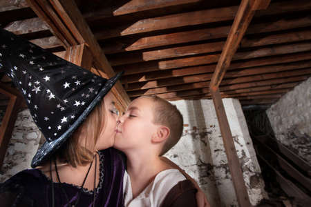Cute little kids dressed as wizards kiss each other photo