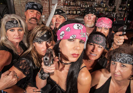 Threatening motorcycle gang members with gun and knife Stockfoto