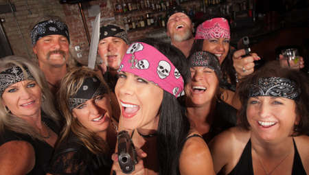 Laughing motorcycle gang members pointing pistols in a bar