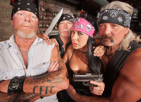 Four tough motorcycle gang members with weapons in tavern photo