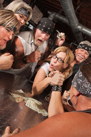 Excited motorcycle gang betting on arm wrestling match with nerd photo