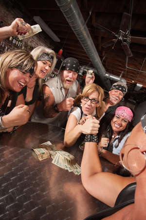 arm: Motorcycle gang cheering in arm wrestling match with nerd
