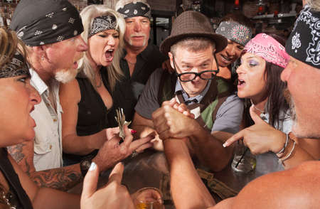Nerd winning an arm wrestling match with strong biker  photo