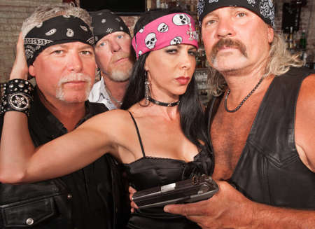 polygamy: Three motorcycle gang members with beautiful woman in leather Stock Photo
