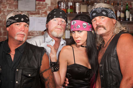 Tough male biker gang members with beautiful woman photo