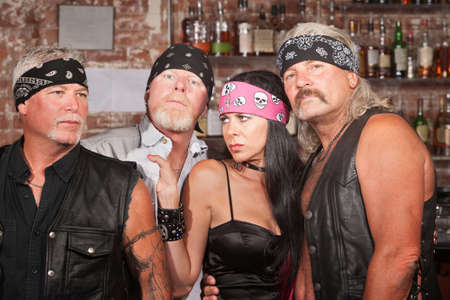 Sexy lady with 3 tough motorcycle gang members in bar photo
