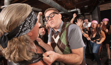 Outraged nerd grabbing gang member by the jacket in bar Stock Photo - 17383384