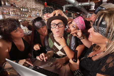 Pretty biker gang women adoring nervous male nerd in bar photo
