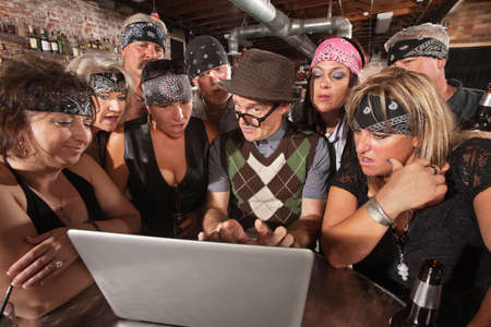 interested: Group of impressed biker gang members watching nerd using a computer Stock Photo