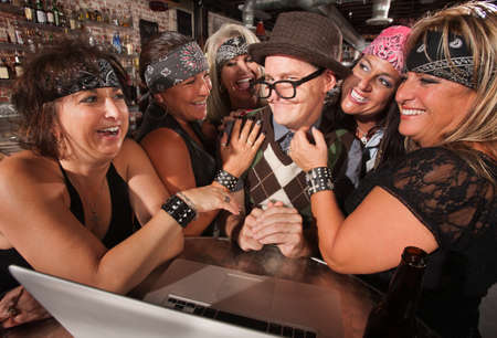 Motorcycle gang members flirting with happy nerd on laptop Stock Photo - 17544372