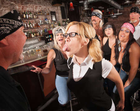 Aggressive female nerd sticking her tongue out at gang member photo