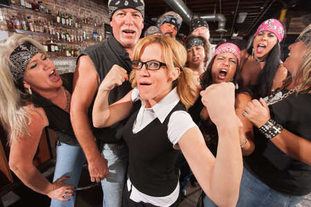 boasting: Cute female nerd flexing muscles with gang of bikers