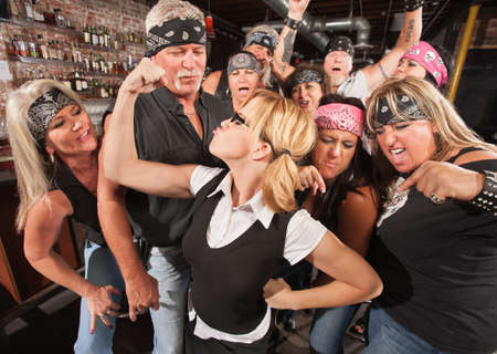 boasting: Biker gang cheering on skinny female nerd flexing muscles Stock Photo