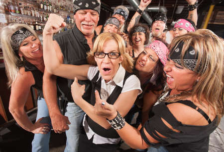 female muscle: Amazed motorcycle gang looking at nerd showing off muscles Stock Photo