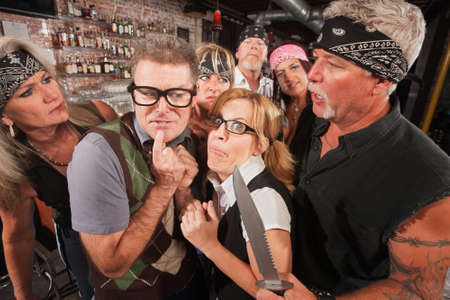 Scared geek couple in bar surrounded by tough gang Stock Photo - 17544364