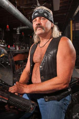 moteros: Tough hombre de mediana edad en la motocicleta en la barra de Foto de archivo