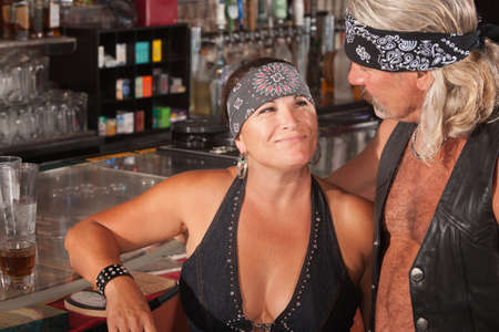 Mature biker gang female admiring man in bar Stock Photo - 17591122