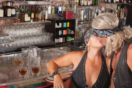 Pair of motorcycle gang lovers kissing at a bar Stock Photo - 17591133