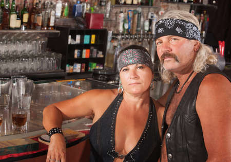 Serious middle aged biker gang couple at bar Stock Photo - 17591149