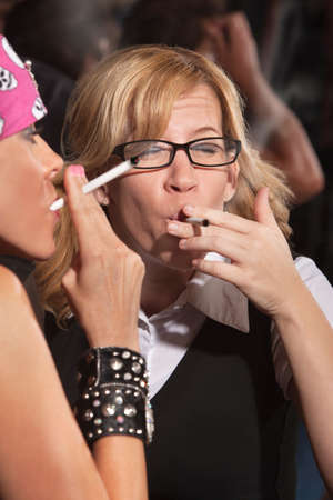 puffing: Nerd puffing deeply on a cigarette with lady in pink bandanna