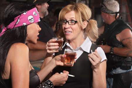 Blond woman and biker gang lady talking while smoking and drinking Stock Photo - 17591135