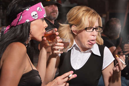 gagging: Female nerd sticking out tongue after tasting whiskey in bar Stock Photo