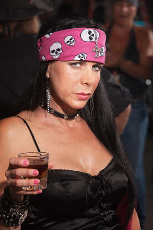 bar: Serious beautiful woman in motorcycle gang outfit in bar