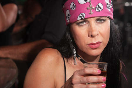 Sad mature white woman with pink bandanna and glass of alcohol Stock Photo - 17591134
