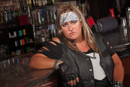 Frowning female motorcycle gang member sitting in bar photo