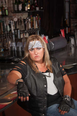 Annoyed female motorcycle gang member sitting in bar photo