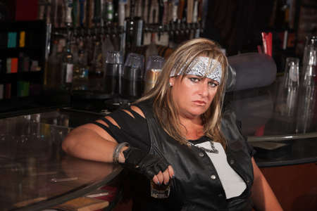 Grumpy biker gang lady holding her drink at a bar photo