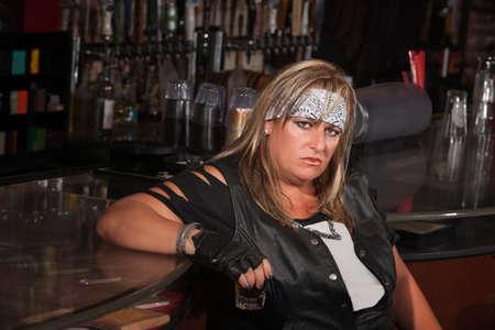 grumpy: Grumpy biker gang lady holding her drink at a bar
