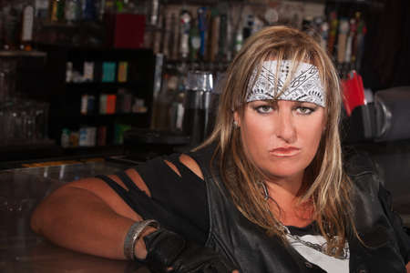 Tough woman in bandanna and leather jacket sitting in a bar Stock Photo - 17591119