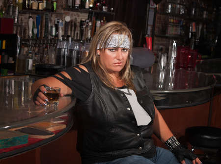 Angry mature woman with alcohol leaning back in a tavern Stock Photo - 17591132