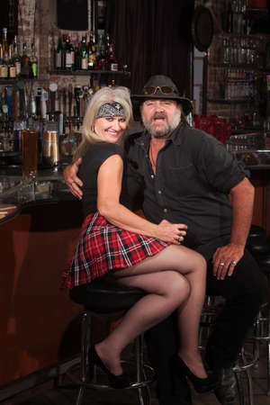 checkered skirt: Happy middle aged motorcycle gang couple sitting at bar counter Stock Photo