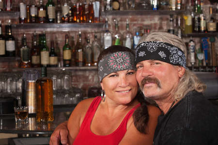 tough: Cute motorcycle gang husband and wife together in bar Stock Photo