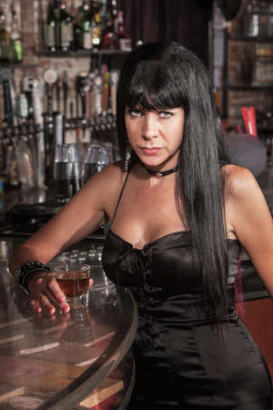 irked: Serious Caucasian woman in black dress at a bar