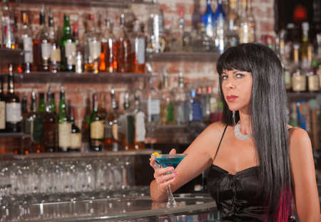 Sultry mature woman in black dress with blue martini Stock Photo - 17591151