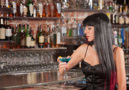 bar: Lonely woman in black hair with martini in bar