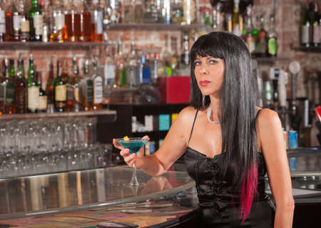 Thoughtful woman in black with martini in a bar photo