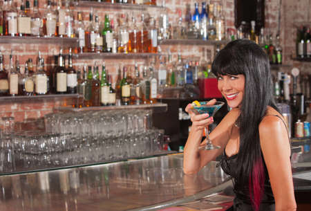 Cute smiling woman in black dress holding a blue martini photo