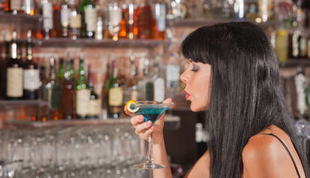 mature sexy woman: Sexy European woman enjoying her drink in a bar