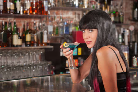 Seductive European female with blue martini in a bar photo